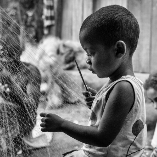 Bambino Sakalava che ripara le reti